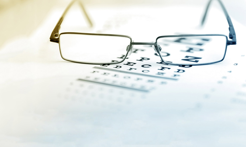 Eyeglasses on top of an eye chart